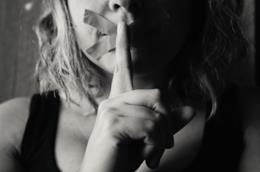 Una donna con la bocca tappata da un cerotto