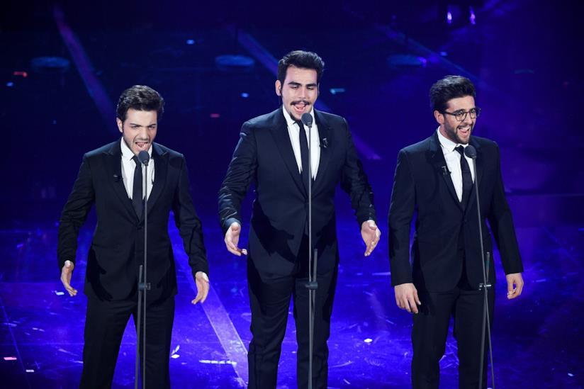 I tre tenori de Il Volo, in piedi, vestiti di nero, di fronte ai microfoni, su sfondo blu