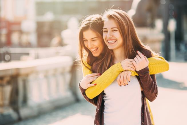 Una ragazza abbraccia per strada la migliore amica