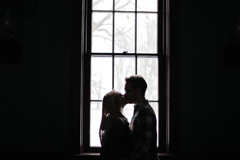 Coppia si bacia davanti una finestra