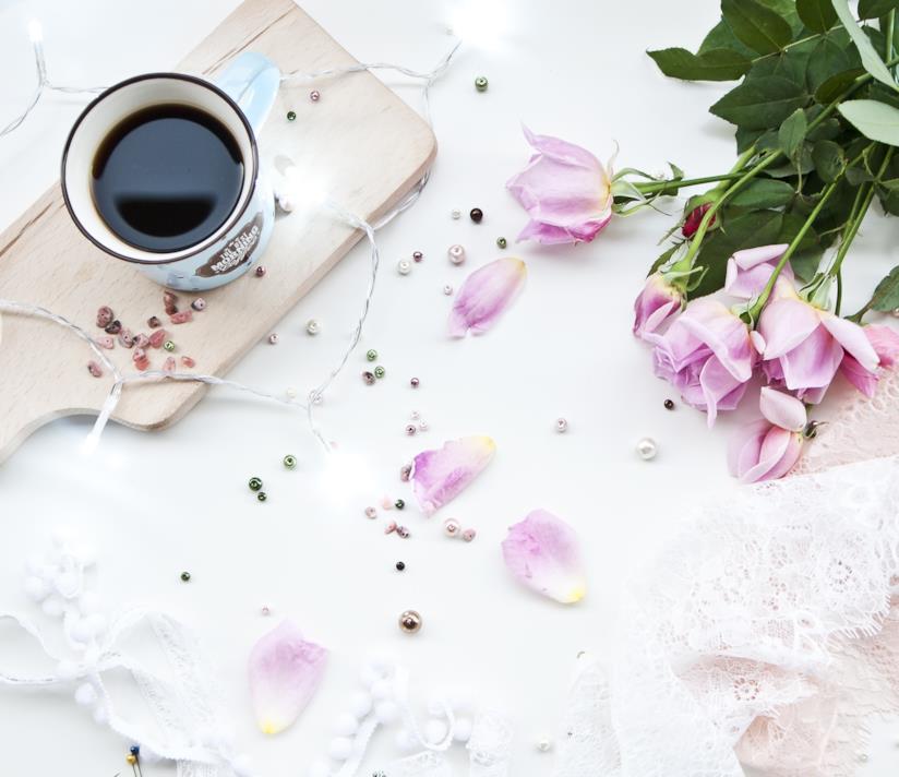 Tazza di caffè su un tavolo con petali di fiori