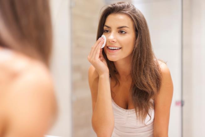 Una ragazza applica sul viso il tonico con un dischetto