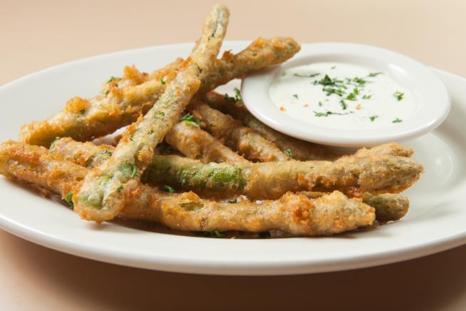 Piatto di asparagi verdi fritti con salsa allo yogurt ed erba cipollina