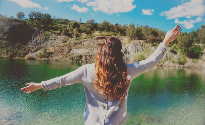Donna di spalle che guarda un lago.