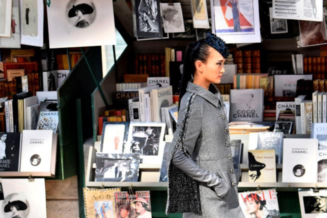 La modella indossa un cappotto grigio della collezione A/I 2018-2019 di Chanel
