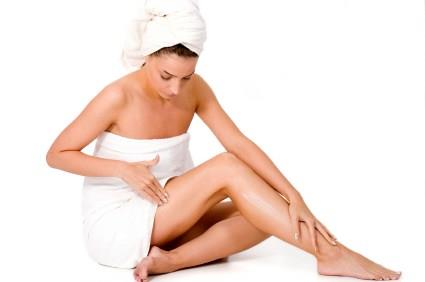 Donna che applica olio di cocco sulle gambe
