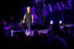 Ligabue, in piedi, in nero, sopra il palco, sorride