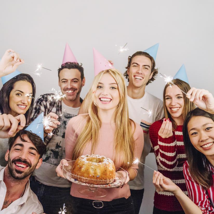 Dei ragazzi con dei cappellini di carta in testa, una ragazza con una torta in mano