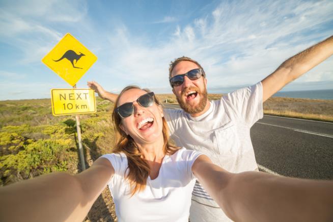 Primo piano selfie di una coppia di ragazzi con alle spalle un cartello che segnala la presenza di canguri