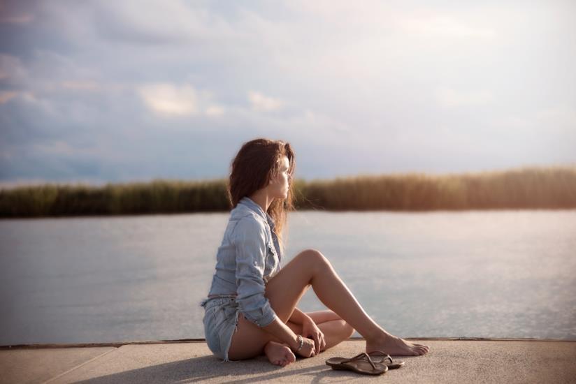 Ragazza seduta su un pontile a piedi nudi