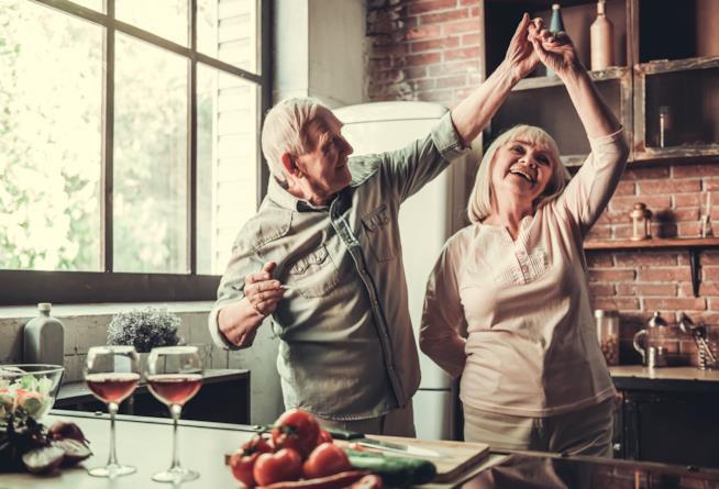 Marito e moglie anziani ballano in cucina