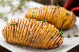 Patate hasselback su piatto di ceramica bianco