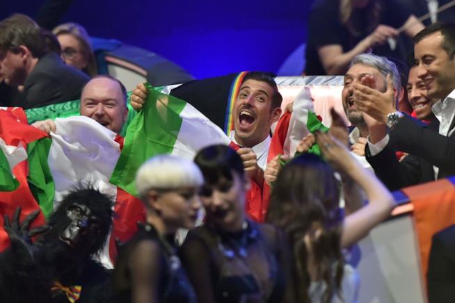 Francesco Gabbani e la delegazione italiana con le bandiere dell'Italia, davanti tre ragazze in nero