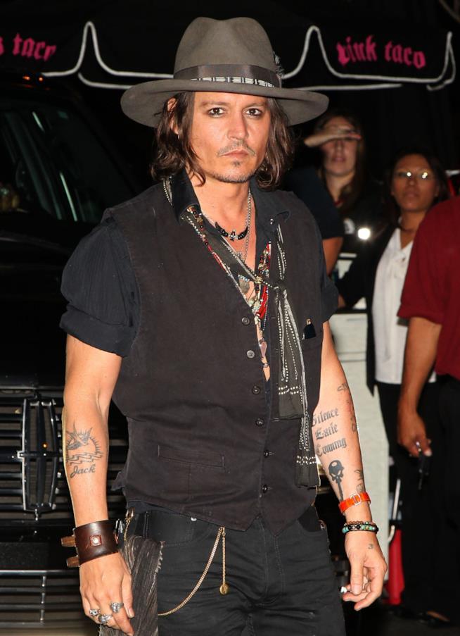 Johnny Depp, in nero, con un cappello