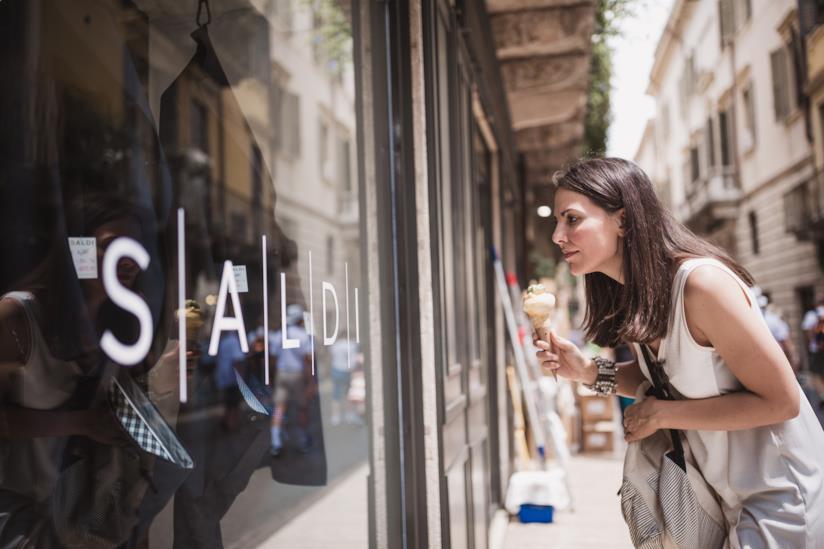 Una donna davanti la vetrina di un negozio.
