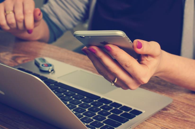 Donna davanti ad un computer e con un cellulare in mano.