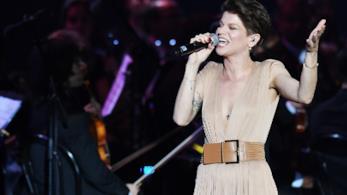 Alessandra Amoroso canta, in piedi e con gli occhi chiusi, al microfono, vestita in marrone chiaro