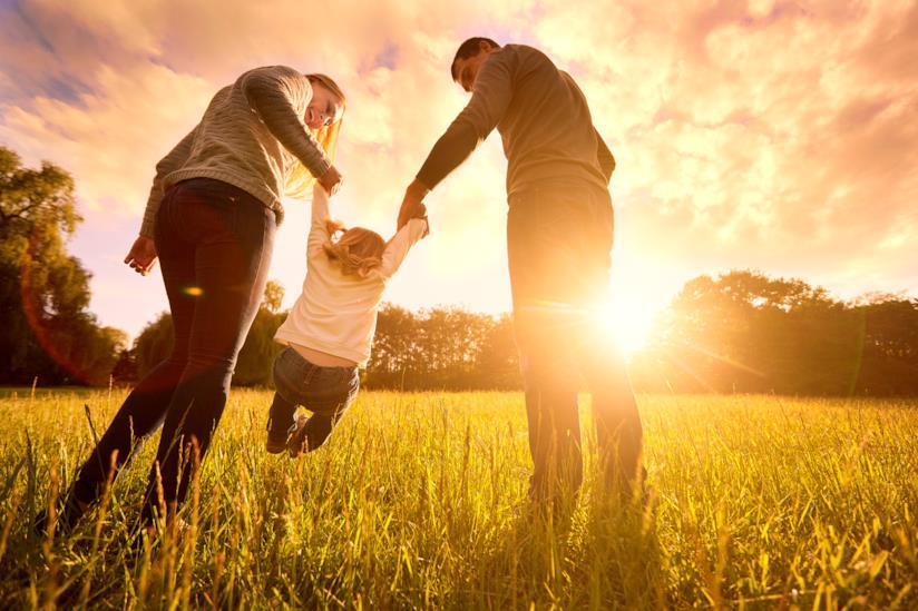 Mamma e papà portano per mano il figlio in un prato