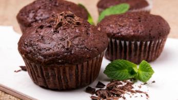 Muffin al cioccolato decorati con scaglie di cioccolato e foglioline di menta