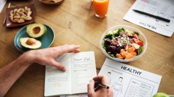 Un uomo scrive su un taccuino l'inizio dieta, su un tavolo con frutta, verdura e una spremuta