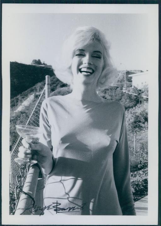Marilyn Monroe tiene in mano un cocktail con indosso un abito a maniche lunghe