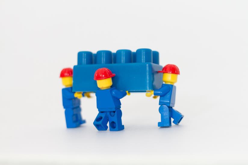 Omini LEGO che trasportano un mattoncino