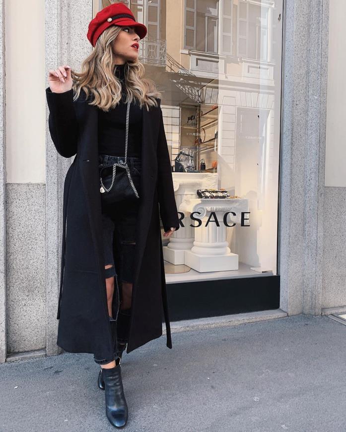 Gaia Cormio davanti allo store Versace con cappotto nero e cappello baker boy rosso