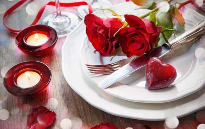 Tavola apparecchiata con rose rosse e candele