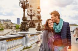 Un uomo e una donna passeggiano abbracciati e sorridenti