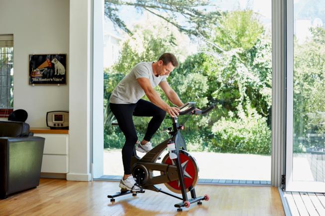 Ragazzo impegnato ad allenarsi in casa con la cyclette