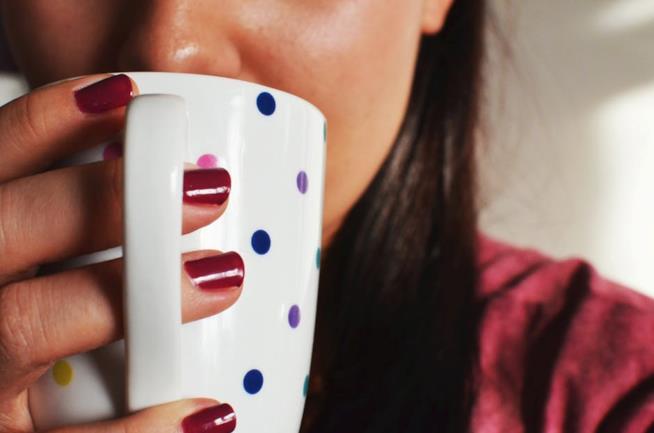 Ragazza che beve da una tazza colorata