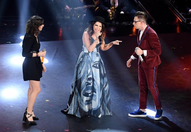 Cristina D'Avena in piedi, canta al microfono con a sinistra Shade (in rosso) e Federica Carta (in nero)