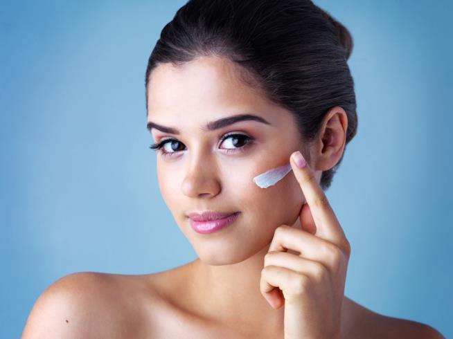 Una ragazza si applica la crema per il viso