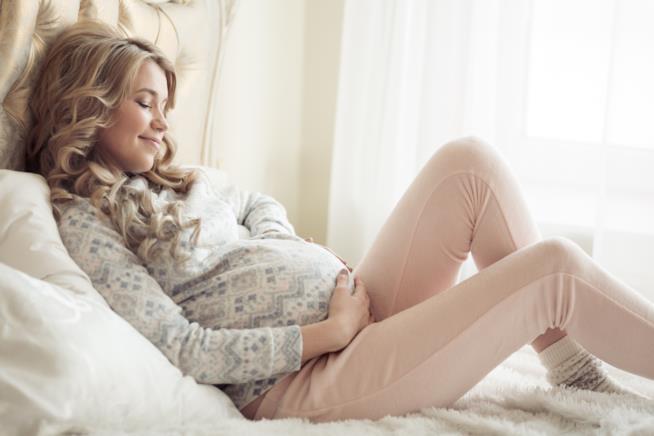 Una donna incinta sdraiata sul letto si accarezza la pancia