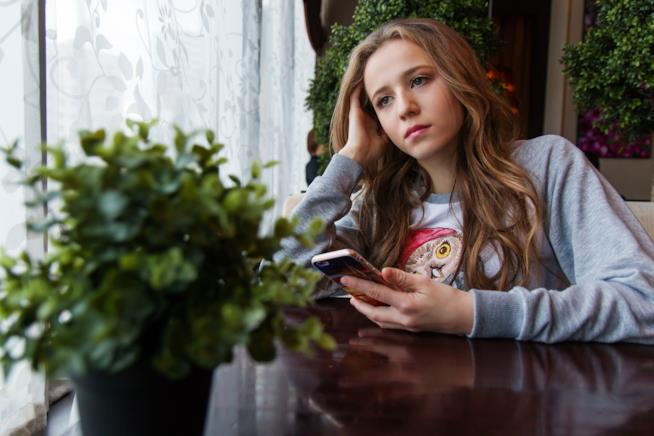 Una ragazza con in mano uno smartphone