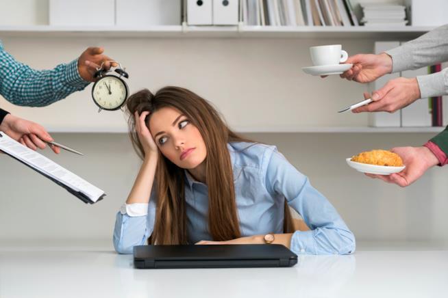 Donna in ufficio circondata da persone che le chiedono cose da fare