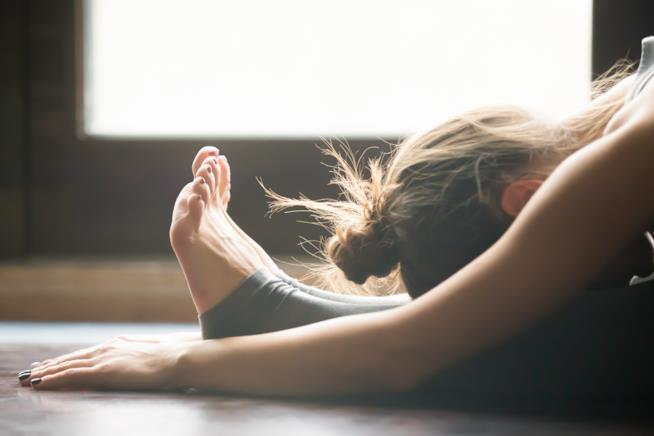 Donne impegnata in un asana della disciplina dello yoga
