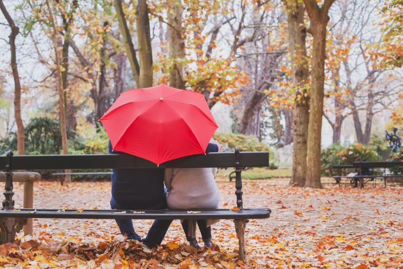 Coppia seduta su una panchina sotto l'ombrello