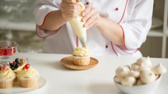 Un pasticcere conclude la preparazione di un cupcake