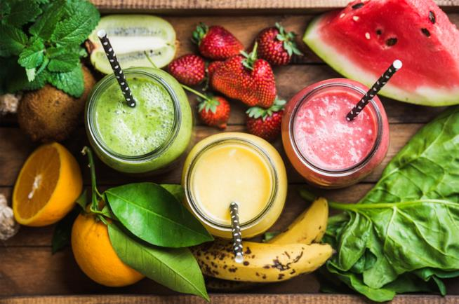 Tre centrifguati di frutta con banane, arance, kiwi, fragole e anguria