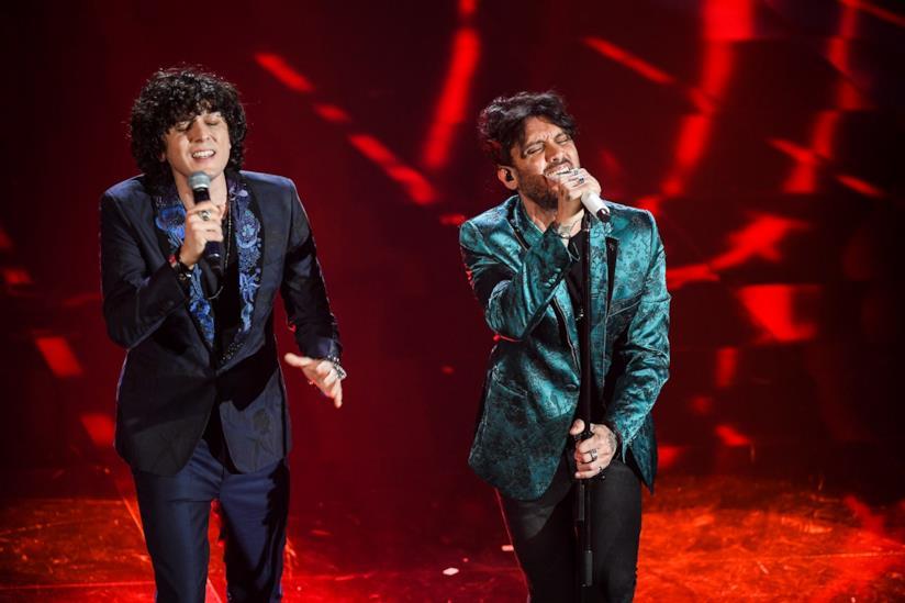 Ermal Meta e Fabrizio Moro cantano, in piedi, su uno sfondo rosso