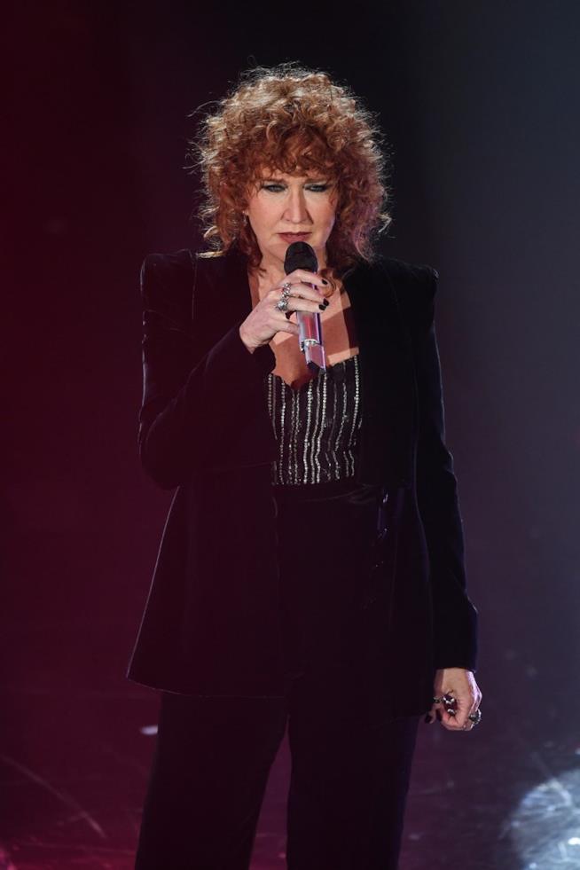 Fiorella Mannoia canta al microfono, vestita di nero, in piedi
