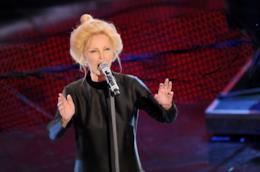 Patty Pravo, in piedi, in nero, canta al microfono su uno sfondo rosso