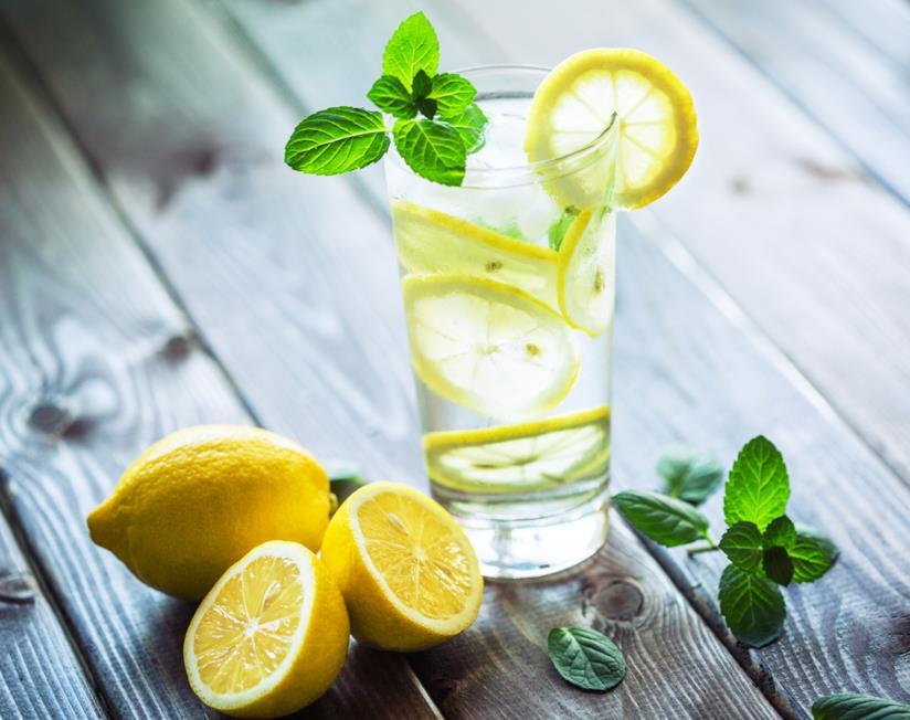 due limoni con vicino un bicchiere di acqua e limone con menta