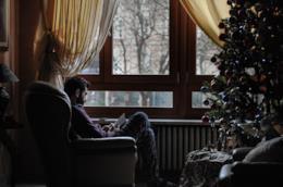 Persona seduta in poltrona accanto alla finestra e al radiatore in un pomeriggio d'inverno