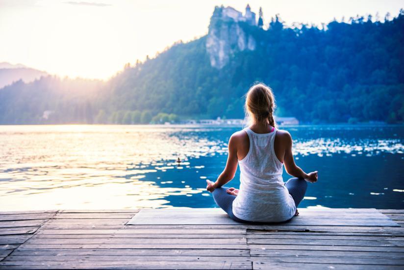 Ragazza in meditazione di fronte a un lago