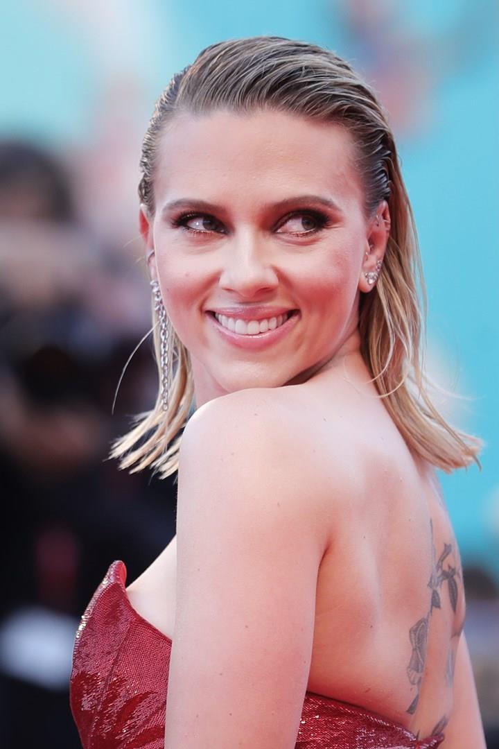 Scarlett Johansson, girata, con un abito rosso e il tatuaggio sulle spalle in evidenza