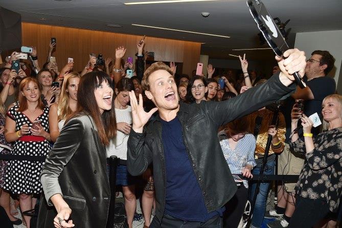 Caitriona e Sam sorridenti che si fanno un selfie con i fan