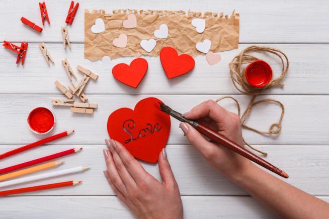 Dettagli di mani femminili che scrivono su un cuore