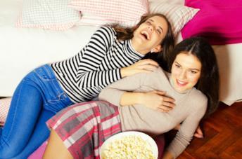 Due ragazze sdraiate sul letto con i pop corn